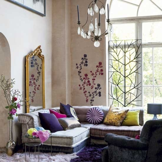 Wall decals is an unusual but more than welcome addition to a boho decor. The cool thing in this room is that flowers on a wall reflects in a vintage mirror.