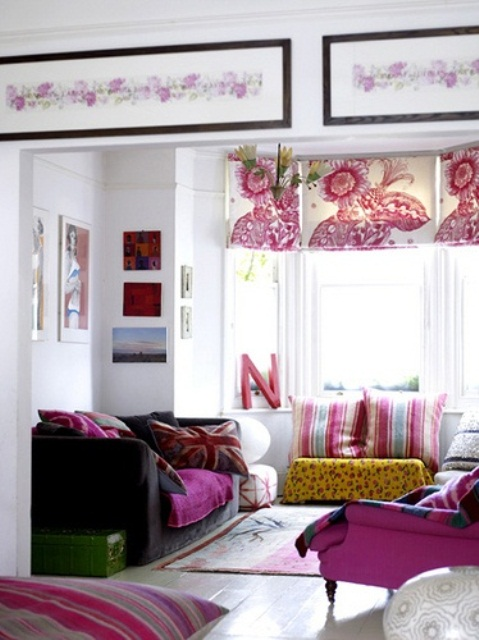 Floral patterned roman curtains and lots of pink textiles create really interesting atmosphere in an all-white living room.