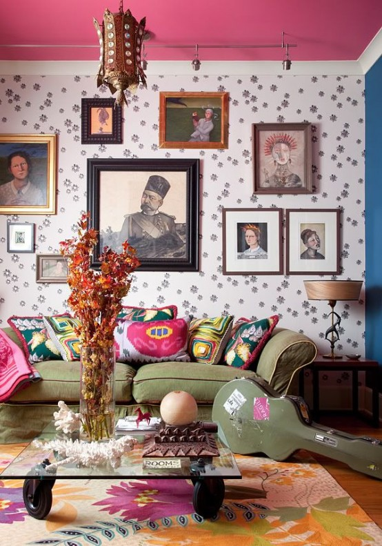 This living room has an extremely imaginative and artistic feel, thanks to the wallpaper's pattern, interesting wall portraits, colorful throw pillows and other antique finds.