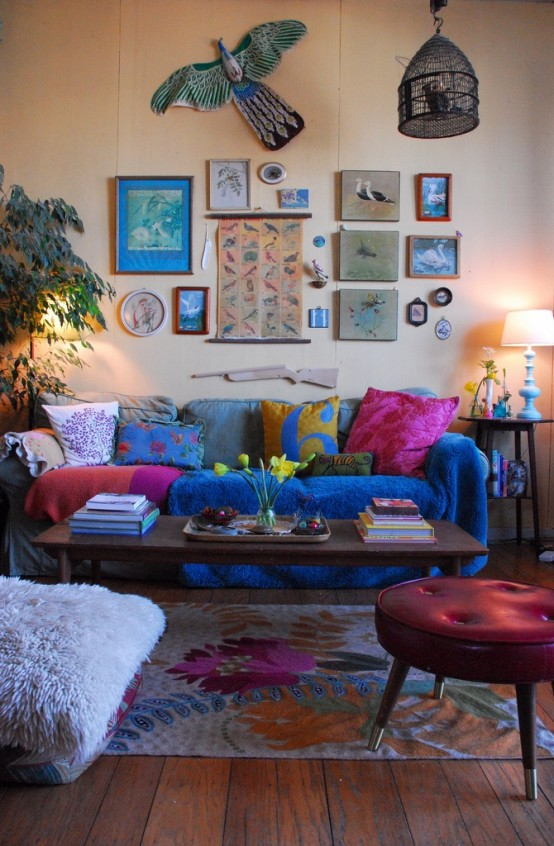 In this colorful living space, the use of vertical spacefrom wall art to a hanging bird cage is quite interesting .
