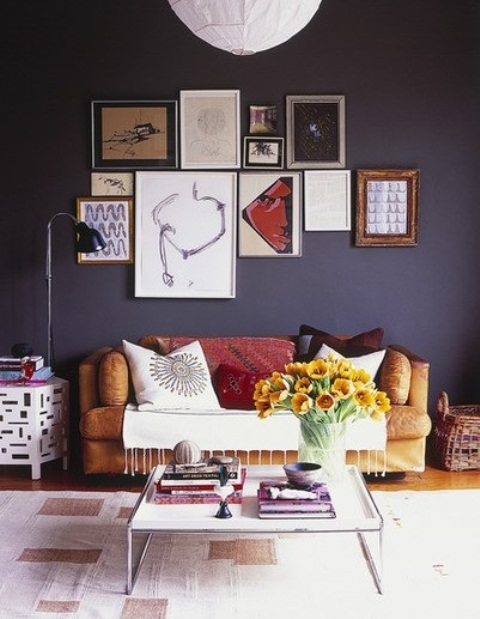 A dark, gloomy wall is not a very popular choice for a living room but it can play out really well. Add some artworks to make it less boring and  slightly soothe the its heaviness.