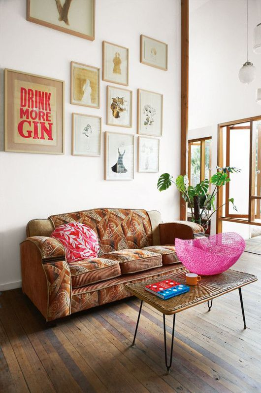 A distinctive gallery wall makes a bold appearance that is so necessary in this clean open-style space. A brown sofa with a cool pattern is also more than welcome addition to the room's decor.