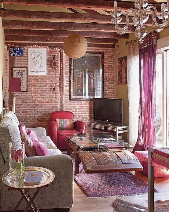 Even though brick walls are more welcome in industrial living rooms, you can play with them in boho environments too. Just make sure to add lots of feminine touches and colors. Throw pillows and pink curtains do the job here.