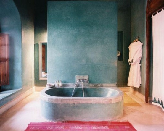 a blue plaster bathroom with a concrete bathtub, wooden shutters and a pink rug