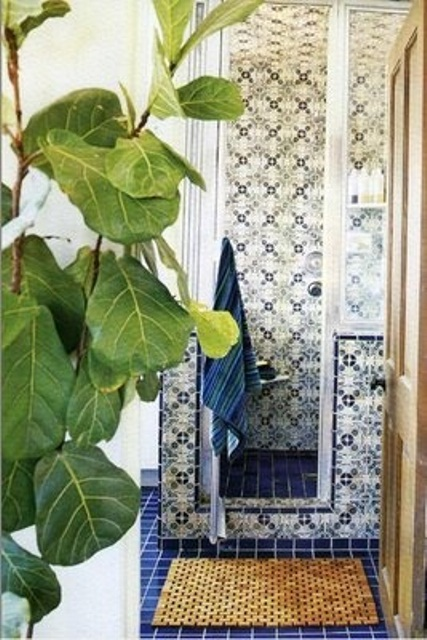 a navy and white Moroccan bathroom with catchy patterned tiles plus potted greenery