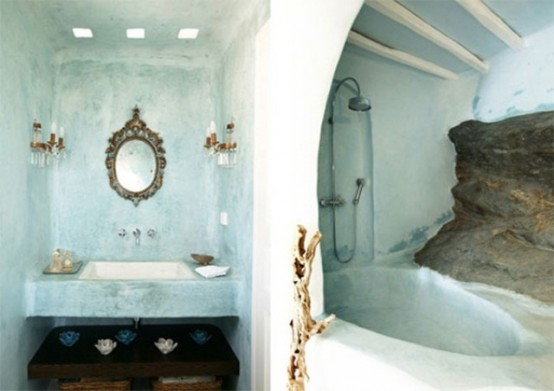 an aqua-colored bathroom done with plaster, with a bathtub of it and an ornated mirror