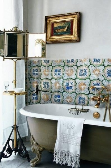 a green bathtub, catchy bright tiles for the backsplash, a mirror on a stand and a sea artwork