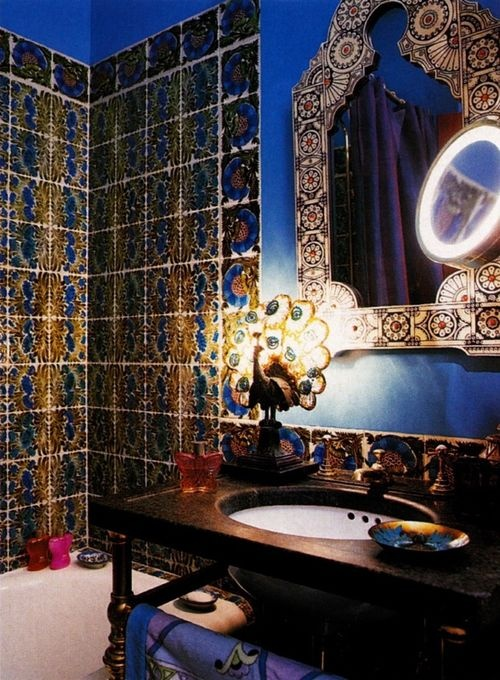 a colorful Moroccan bathroom with bright tiles, an ornated mirror, a cool peacock table lamp