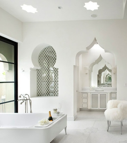 a pure white bathroom with a carved doorway, an arched tiled niche, a carved vanity and a modern chair
