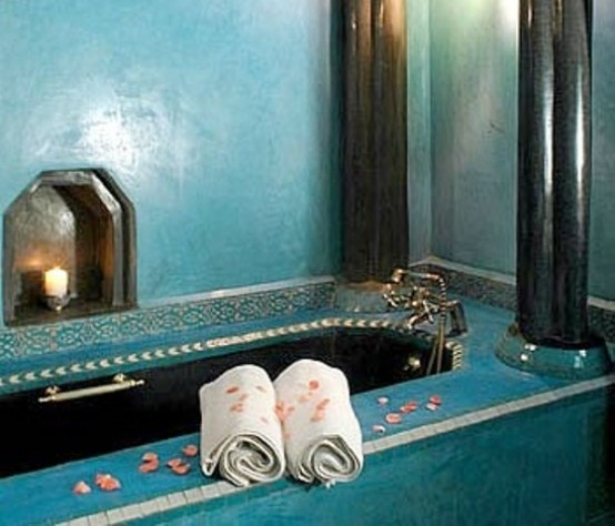 a turquoise bathroom with a tile clad bathtub plus a niche with a candle