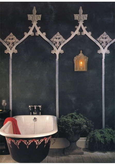 a dark Moroccan bathroom with black walls with patterns, potted greenery and a decorated bathtub