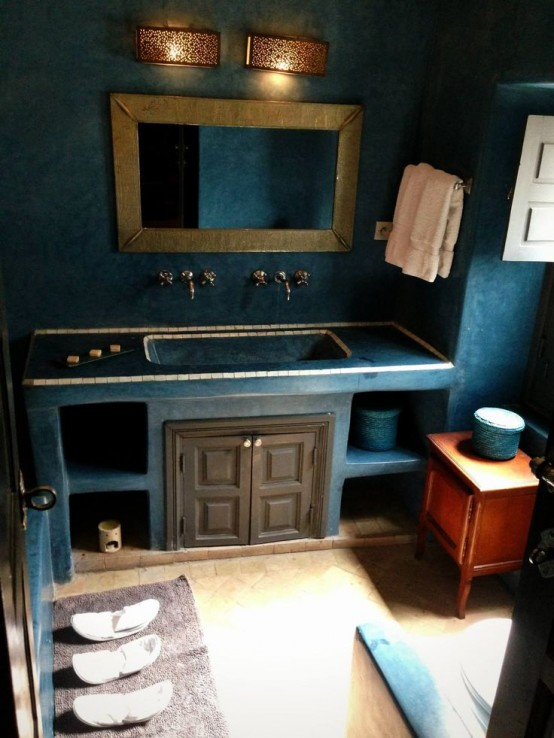 a navy Moroccan bathroom with a built-in vanity, a gilded frame mirror, wall lamps and a wooden sideboard