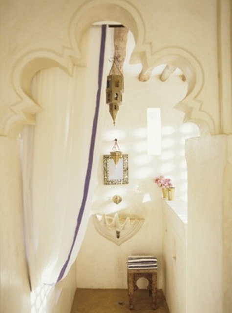 a neutral bathroom with a carved doorway, an embellished mirror, a seashell sink, a Moroccan lantern and a curtain