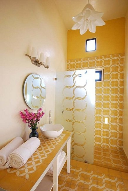 a bright yellow bathroom with catchy tiles, a bloom-shaped pendant lamp and a vanity clad with tiles
