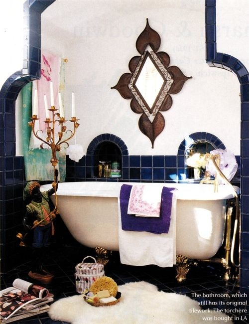 a navy and white tiled bathroom with an ornated mirror, a beautiful candle holder and a faux fur rug