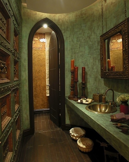 a green Moroccan bathroom with a brass sink, an ornated mirror, a wall with metal doors and pulls
