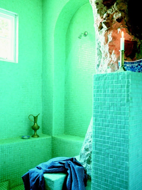 a bright turquoise and green bathroom with candles and a vintage metal jug