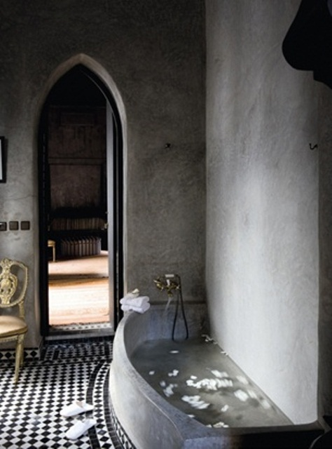 a Moroccan bathroom with concrete walls and a concrete tub, black and white tiles and an arched doorway
