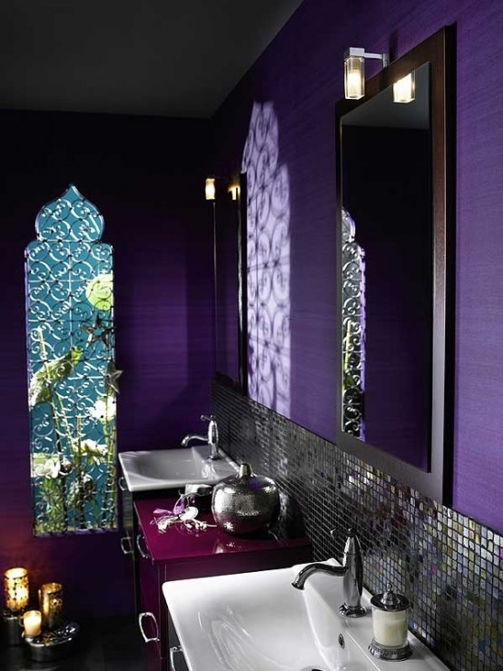 a bright purple bathroom with an arched window, a tiled backsplash, laser cut candle lanterns