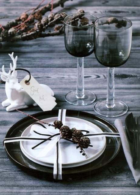 a Nordic rustic tablescape with an uncovered table, branches, a black placemat and plates plus grey glasses