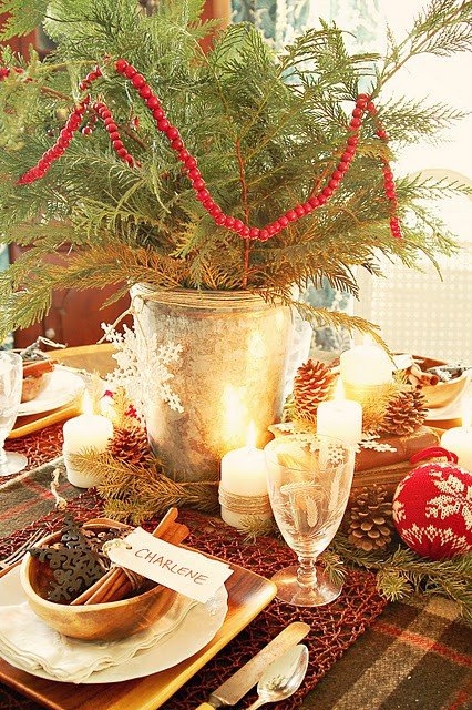 a rustic Christmas tablescape with a plaid tablecloth, a red woven placemat, pinecones, candles, evergreens and a wooden charger