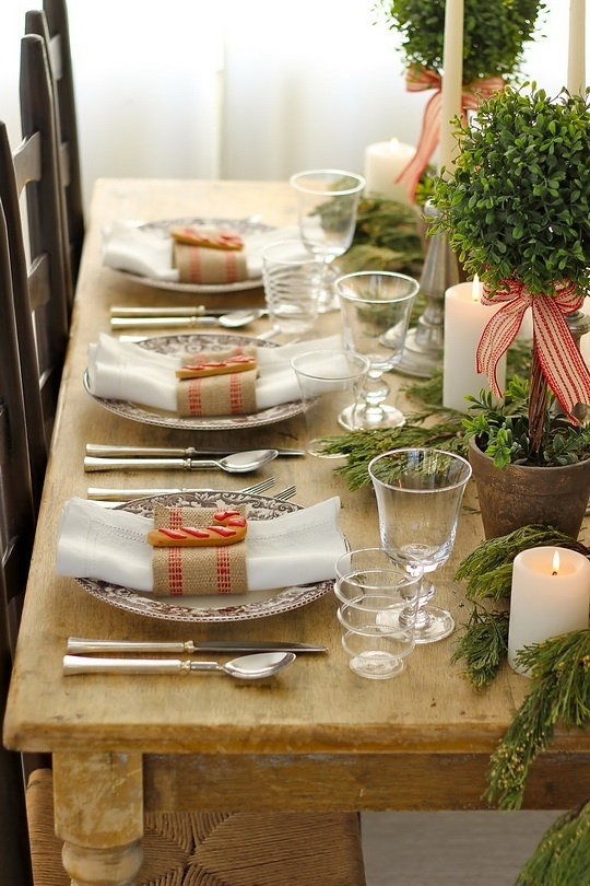 a rustic Christmas tablescape with an uncovered table, evergreens in pots, candles, refined chargers and striped napkins