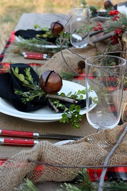 a rustic Christmas table setting with a burlap tablecloth and napkins, berries, evergreens, bells and sticks for a natural feel