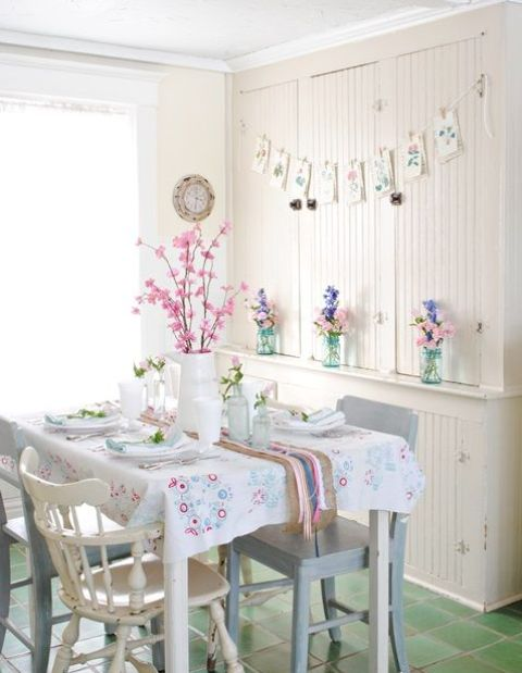 a pastel dining zone with a floral garland, pastel blooms, floral print linens on the table