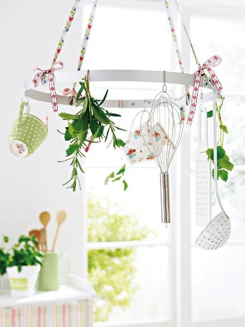 a kitchen chandelier with cutlery, mugs, floral print ribbons and bows is a cool spring decoration