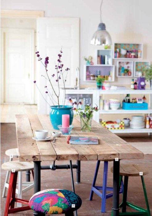 a colorful stool, bright blooms in a blue pots and lots of colorful items and bright shelves make the space springy