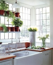 fresh greenery in pots and bright yellow tulips in a bucket will make yoru kitchen more spring-like, bright and fresh