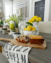 yellow blooms and lemons on the table make the tablescape look bright, fun and spring-infused