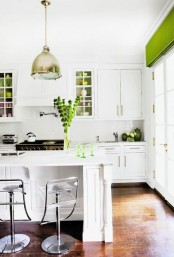 a green Roman shade, gree glasses, greenery in a vase and green mugs add color and refresh the kitchen for spring
