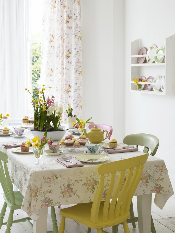 floral linens, pastel chairs, pastel tableware and plates make the dining space look more spring like