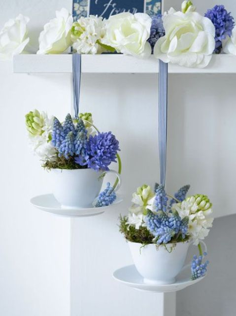 white and purple blooms on the shelf and blooms and moss in mugs hanging down make the kitchen springy