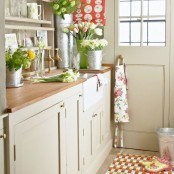 lots of fresh blooms and greenery in various buckets and floral linens make the kitchen bright, bold and spring-infused