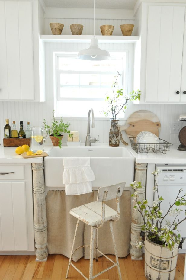 fresh greenery and blooms in vases and pots make the kitchen look more spring like and blooming itself