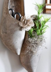 traditional Dutch wooden shoes with greenery in them hanging on the wall are a creative and cool spring decor idea