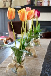 bright blooms in jars wrapped with burlap and with a burlap table runner make the tablescape spring-like