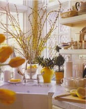 bright yellow blooming branches, bright yellow vases, lemons and pots make the kitchen bright, fun and spring-like
