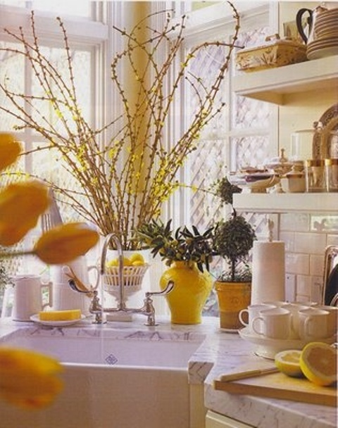 bright yellow blooming branches, bright yellow vases, lemons and pots make the kitchen bright, fun and spring like