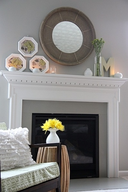 a spring mantel with vintage botanical artworks and some floral arrangements