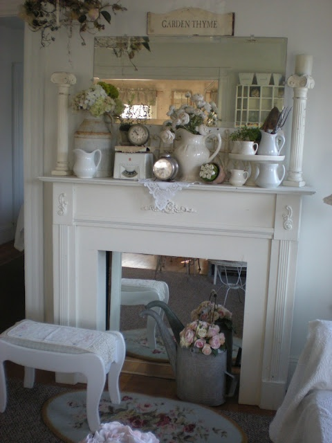 a vintage spring mantel with floral arrangements, jugs, clocks, pillars and a mirror
