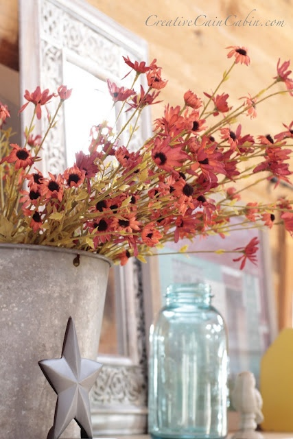 bright and colorful blooms in a bucket for styling a spring mantel