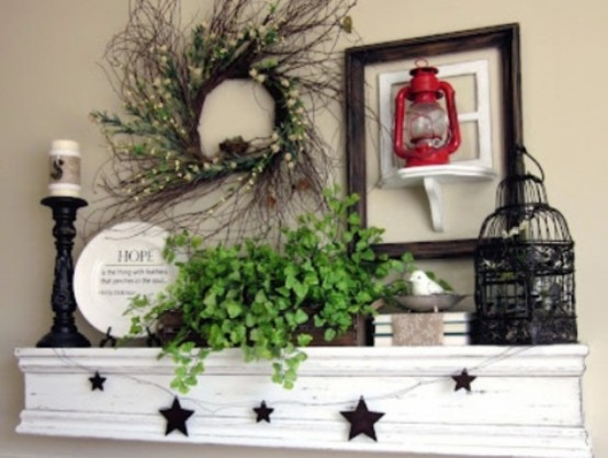 a blooming and greenery wreath over the mantel, potted greenery, a fake bird and a bird cage