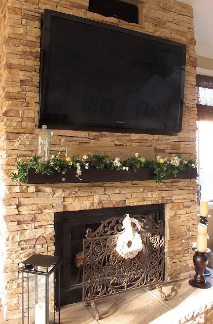 a mantel turned into a planter with greenery and blooms in it and a sign