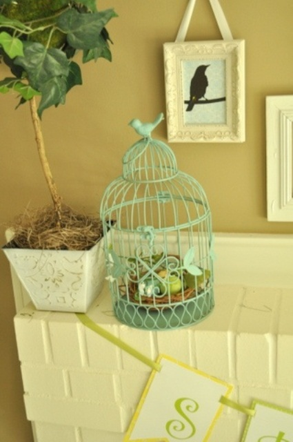 a potted tree and a green bird cage with a nest and eggs