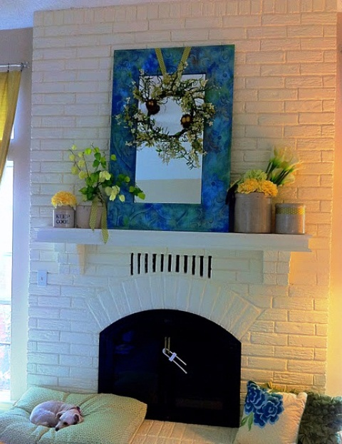 a fresh spring mantel with bright floral spring arrangements and a blooming wreaht over the mantel