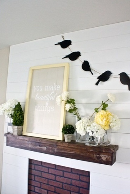 a rustic spring mantel with bloom arrangements and potted greenery, a sign and a bird garland