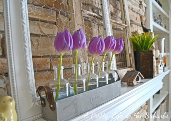 a purple tulip arrangement in bottles and some potted greenery for a cool spring mantel